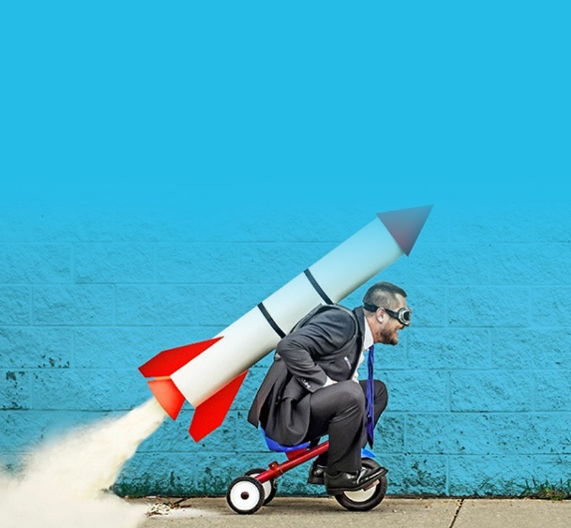 Man riding a tricycle with a rocket on back
